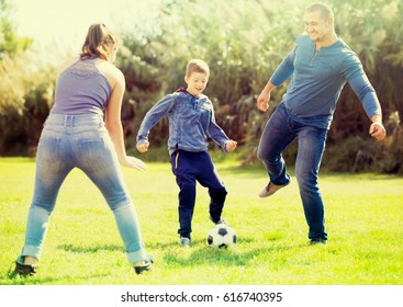 Son and parents playing football in grass field