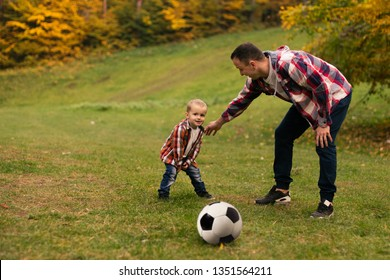 Son playing with ball on grass