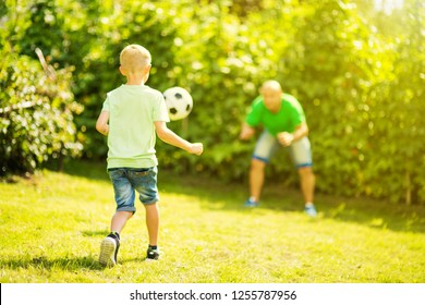 Son playing with his father footbal in a park, having fun