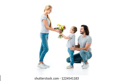 Son presenting bouquet of flowers his mother isolated on white