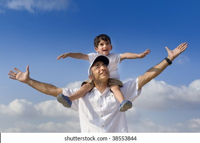 son riding on his father shoulders with spread arms