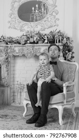 The son sits on father's knees on Christmas Eve - black and white