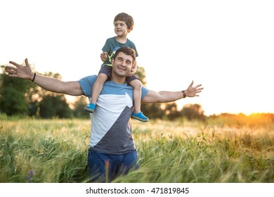 Son sits on the shoulders of his father on the sunset background. Man stands in the rye field with hands stretched to the sides. They both smiling and wears T-shirts with shorts. Outdoors. Horizontal.