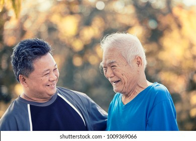 A son take care his father who has alzheimer's disease. Father very happy when go to park, use effect filter.Concept freelance nurse with old people.