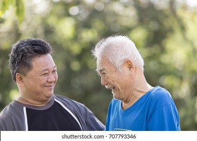A son take care his father who has alzheimer's disease. Father very happy when go to park. Concept happy family.
