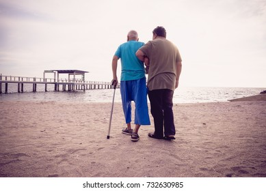 A son take care his father who has alzheimer's disease.Memory problems due to Dementia and Alzheimer's disease as a medical health care concept with a headache and brain scared. Concept happy family.