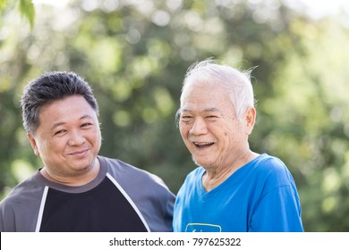 A son take care his father who has alzheimer's disease. Father very happy when go to park, they make selfie with smart phone. Concept freelance nurse with old people.