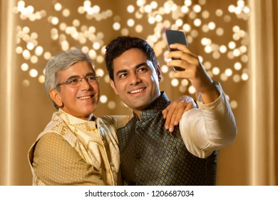 Son taking a self portrait with Father using smart-phone in diwali festival
