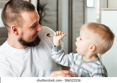 Son trying to feed his surprised by this fact father. Son gives him an ice cream on a spoon.