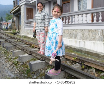 Sonada, Darjeeling : 31 May 2019: A Nepali mother and her daughter holding a doll walking on the toy train track stopped to face the camera in darjeeling on the occasion of mothers day.