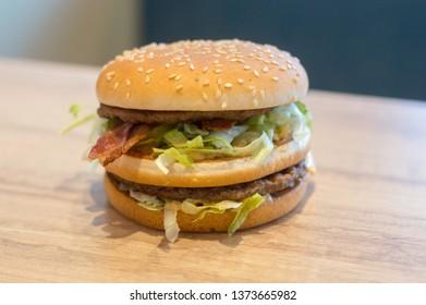 Sonderborg, Denmark - February 14, 2019: McDonald's Big Mac Bacon sandwich on wooden table.