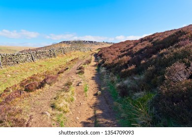 A sone wall runs at the side of a rugged footpath to Higger Tor in the Derbyshire Peak District