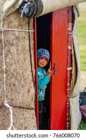 SONG KUL, KYRGYZSTAN - AUGUST 10: Portrait of a young boy looking out the yurt, typical central asian nomad house. August, 2016