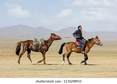 Song Kul, Kyrgyzstan, August 8 2018: A Kyrgyz rides his horse and leads another on a leash at Song Kul Lake in Kyrgyzstan