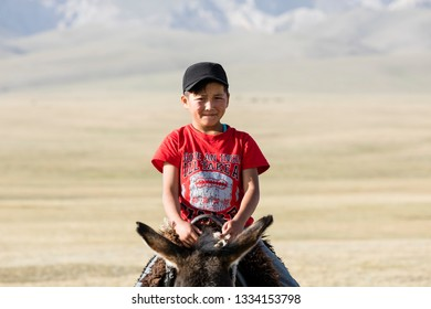 Song Kul, Kyrgyzstan, August 8 2018: A boy in a red T-shirt rides a donkey through the steppe at Song Kul Lake in Kyrgyzstan
