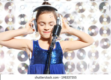 Song - musical child .Child, teen, girl, singing into a microphone, a small singer