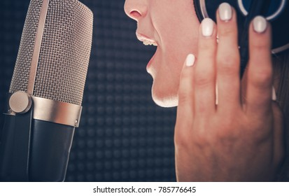 Song Recording by Singer. Professional Audio Recording in a Studio. Caucasian Female Singer with Headphones Closeup Photo. Music Industry Theme.