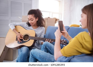 Song for you. Upbeat curly-haired girl playing guitar and dedicating a song to her roommate while she filming her on phone