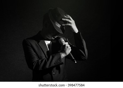 Songer hand holding the microphone and singing on black background, musical concept