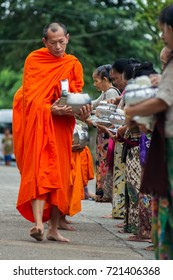 Songkhla Buri, Thailand - November 21, 2012: Buddhist monks receiving alms and food given by the local people in the early morning.