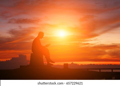 SONGKHLA, THAILAND - April 21,2017 : Silhouette before Sunrise and Man reads books statue on April 21, 2017 in Songkhla, Thailand.