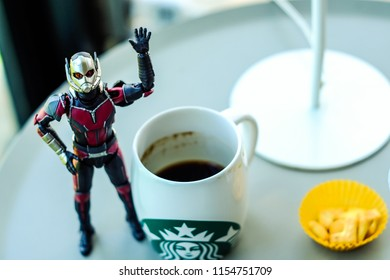 Songkhla, Thailand - August 13, 2018:  Ant man action figure from Marvel ant man comic and movie. With a drink coffee starbuck.