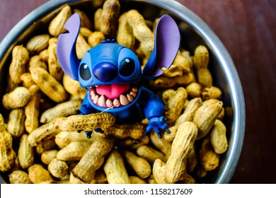 Songkhla, Thailand - August 17, 2018:  Stitch With his pile of nuts. stitch disney