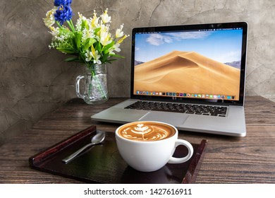 SONGKHLA, THAILAND - December 8, 2018: Latte art coffee with macbook computer on wooden table, created by Apple Inc.