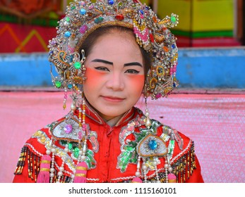 SONGKHLA, THAILAND - JAN 31, 2013: Young, red-and-golden costumed female Thai Chinese opera performer with elaborate make-up poses for the camera during Chinese New Year, on Jan 31, 2013.