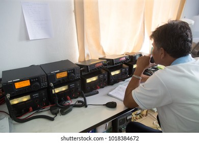 Songkhla, Thailand -January 8, 2018: Fishing Government official using radio to communicate with fishing vessels in the ocean to check up for security transportation at Fishing vessels control center.