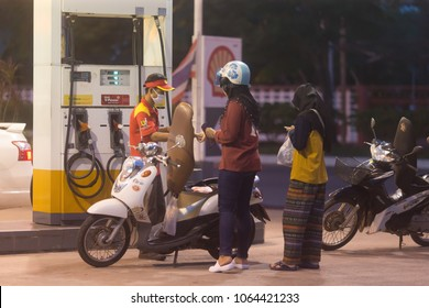 Songkhla, Thailand - January 8, 2018: Two Muslim female at Shell Gas Station fill oil to Fino Motorcycle at night time.