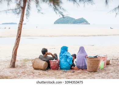 Songkhla, Thailand - JULY 25, 2011: Rear view of Muslim family while picnicking with wicker baskets on the beach. Laem Samila.