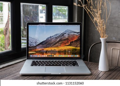 SONGKHLA, THAILAND - July 7, 2018: Apple Macbook pro computer with dried flower vase on wooden table, created by Apple Inc.