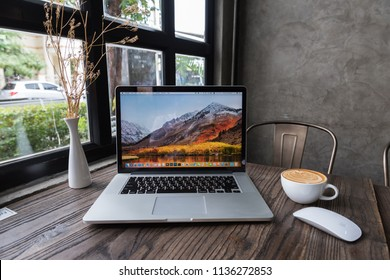 SONGKHLA, THAILAND - July 7, 2018: Apple Macbook pro computer with dried flower vase and latte art coffee on wooden table, created by Apple Inc.