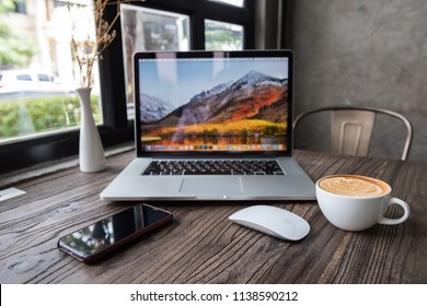 SONGKHLA, THAILAND - July 7, 2018: Apple Macbook pro computer with Magic mouse, iPhone X and latte art coffee on wooden table, created by Apple Inc.
