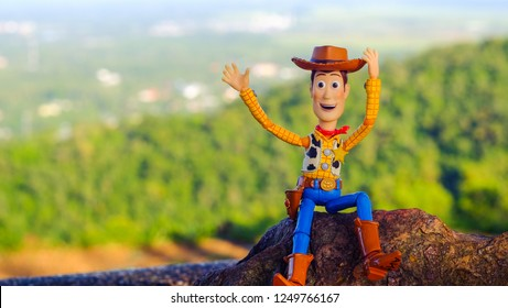 Songkhla, Thailand - November 30, 2018: Woody figure model. Woody sitting on the rock waving at you. Feeling relax and fresh.This figure by disney Pixar inc.