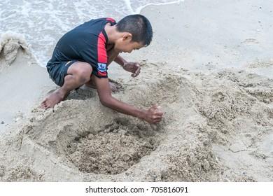 Songkhla, Thailand on 6 August 2017; A boy digs in sand on Samila Beach.