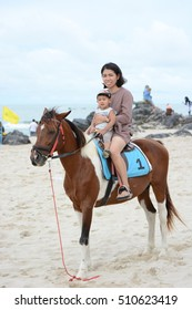 Songkhla ,THAILAND-October 31,2016 : Asia mother and son ride horse on the beach