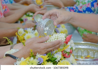 Songkran Festival in Thailand. Hand of young people pouring water on the older people hands. Holiday of Thailand and religion concepts.