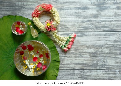Songkran festival Thailand theme Songkran water bowls decorated with jasmine, rose and marigold petals over green lotus leaf on wood planks with Thai traditional jasmine garland and scented water.