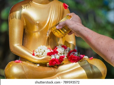 Songkran festival in Thailand,Hand woman use the water pouring to golden buddha statue.