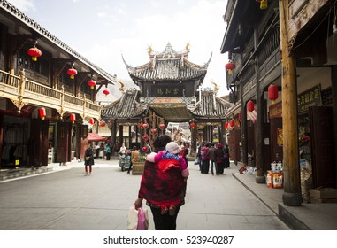 SONGPAN, CHINA - April 3, 2016: Central street of Songpan ancient town, woman is carrying a baby on her back in Songpan, China on April 3, 2016