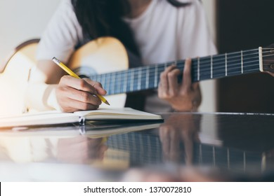 songwriter artist thinking and writing notes,lyrics in book at studio.man playing live acoustic guitar.concept for musician creative.artist composer work process.people relaxing time with instrument