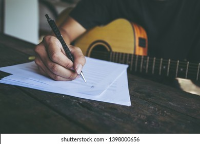 songwriter artist thinking writing notes,lyrics in book at studio.man playing live acoustic guitar.concept for musician creative.artist composer in work process.people relaxing time with instrument