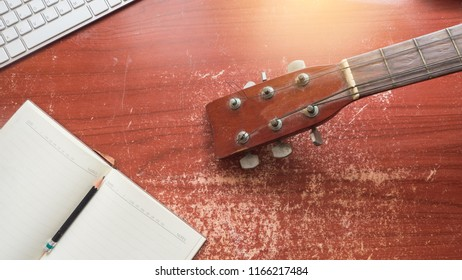 Songwriter with guitar notebook and keyboard for songwriting concept