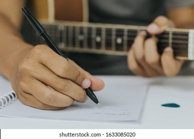 Songwriter in a songwriting process. A male composer write lyrics on a notebook while playing guitar in a studio. Artist composer work in process. Musician playing guitar to make a song.