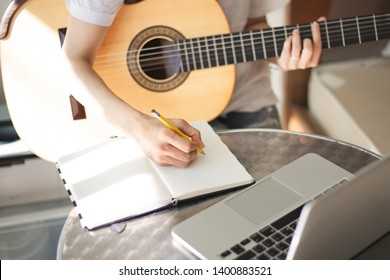 songwriter thinking and writing notes,lyrics in book at studio.man playing live acoustic guitar.concept for musician creative.artist composer in work process.people relaxing time with instrument
