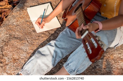 Songwriter writing on notebook with acoustic guitar.