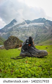 Sonmarg, Jammu and Kashmir, India: Date- May 20, 2019: Quechua hiking shoes of a hiker on green grass during a trek with mountains in the background