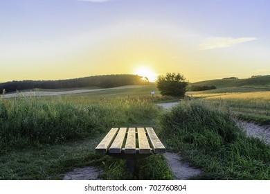 Sonnenbank! Eine einsame Bank steht an einem Feld mit Blick in Richtung Sonnenuntergang!